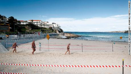 A group of men walks on Bondi Beach on May 1 in Sydney, Australia, following easing steps in response to a decrease in corona virus cases across the state.