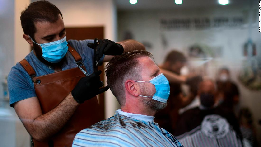 A hairdresser wears a face mask as he cuts a customer's hair in Dortmund, Germany, on Monday.