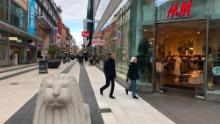 The main shopping street in Stockholm is full of people.