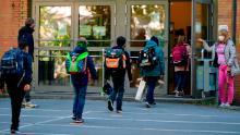 Children respect social distance rules when they enter Petri elementary school in Dortmund, western Germany, on Thursday, when the school reopens for a number of students.
