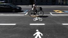 A woman cycles through a bicycle lane in Milan.