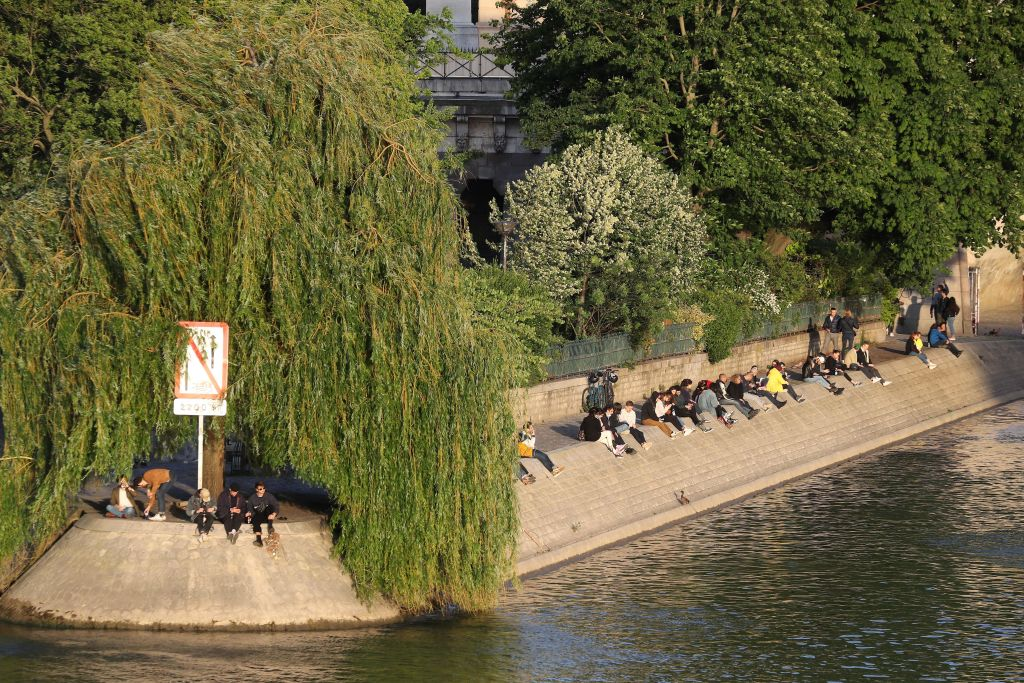 People share drinks on the banks of the Seine in Paris on Monday, on the first day of easing French locking measures.