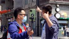 People wearing face masks streamed live on Qianmen Street on April 25 in Beijing, China.