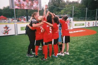 A football team huddle on the pitch