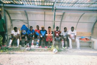 A group of football players watch by the side of the pitch