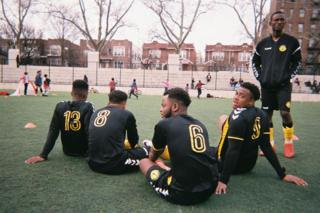 Football players sit on the ground on a football pitch