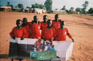 A group of children hold a placard