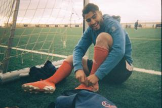 A football player puts his boots on