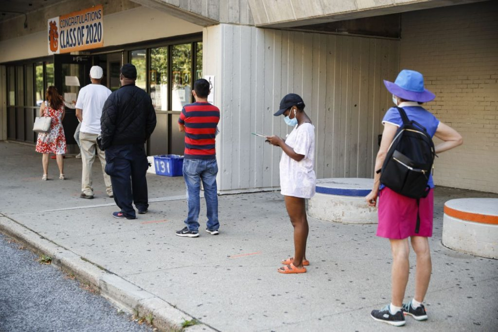 Voters wait in line to cast their ballots in New York's primary election at a polling station inside Yonkers Middle/High School, Tuesday, June 23, 2020, in Yonkers, N.Y. (AP Photo/John Minchillo)