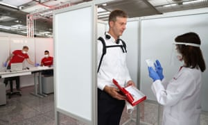 A saliva sample is taken at Germany's first walk-through Covid-19 test centre at Frankfurt airport.