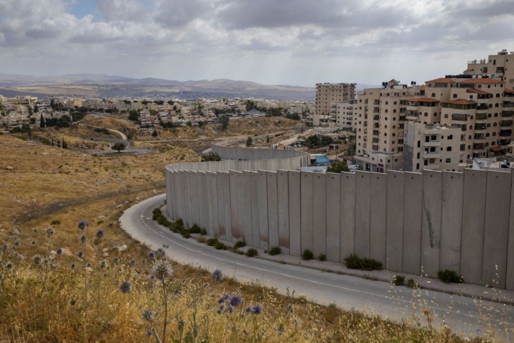 In this Friday, June 19, 2020 photo, A view of Shuafat refugee camp is seen behind section of Israel's separation barrier in Jerusalem, Friday, June 19, 2020. (AP Photo/Oded Balilty)
