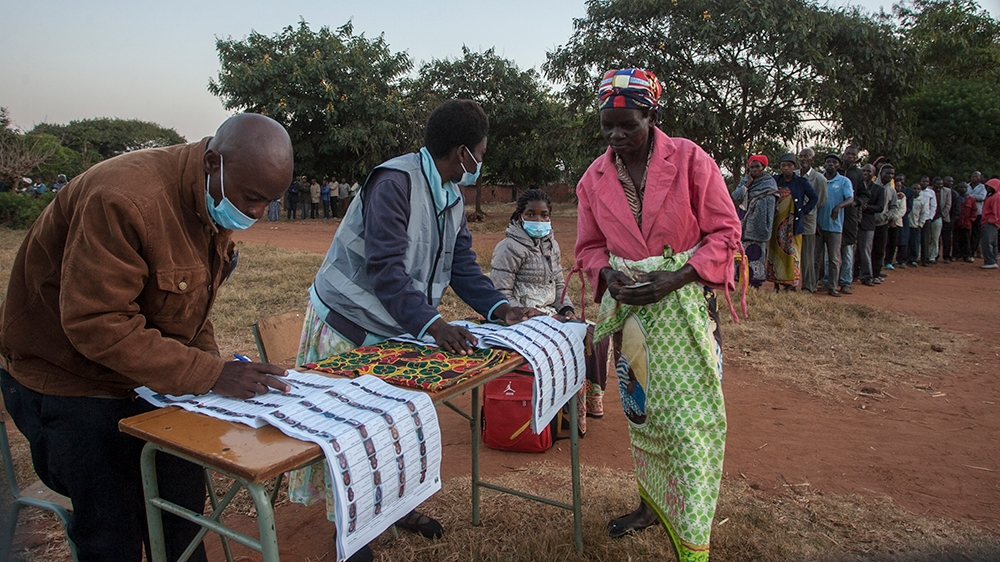 Electoral officials check the voters roll while people queue to vote at the Malembo polling station during the presidential elections in Lilongwe on June 23, 2020. - Malawians return to the polls on J