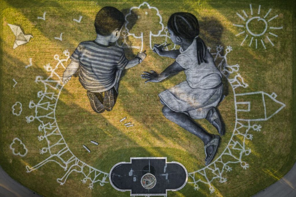 """In this picture made available Friday, June 26, 2020 an aerial view shows a giant ephemeral landart painting by Swiss French artist Saype entitled """"World in Progress"""" representing two children drawing their ideal world, at the European headquarters of the United Nations in Geneva, Switzerland, Wednesday, June 24, 2020. The artwork covering 6000 square meters was produced with biodegradable paints made from natural pigments such as coal and chalk. The fresco, offered by Switzerland, for the the 75th anniversary of the signing of the United Nations Charter in San Francisco on 26.6.1945 will be inaugurated by Swiss Federal Councillor Ignazio Cassis, in the presence of the Director-General of the United Nations Office in Geneva, Tatiana Valovaya. (Valentin Flauraud/Keystone via AP)"""