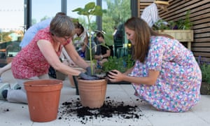The Duchess of Cambridge helps to pot plants and herbs during a visit to The Nook hospice in Framlingham Earl, Norfolk.
