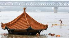 Residents swim past a riverside pavilion submerged by the flooded Yangtze River in Wuhan in central China's Hubei province on July 8.