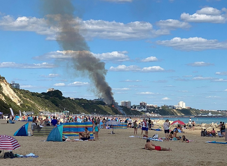 Thick black smoke is billowing upwards into the sky as beach-goers watch in horror