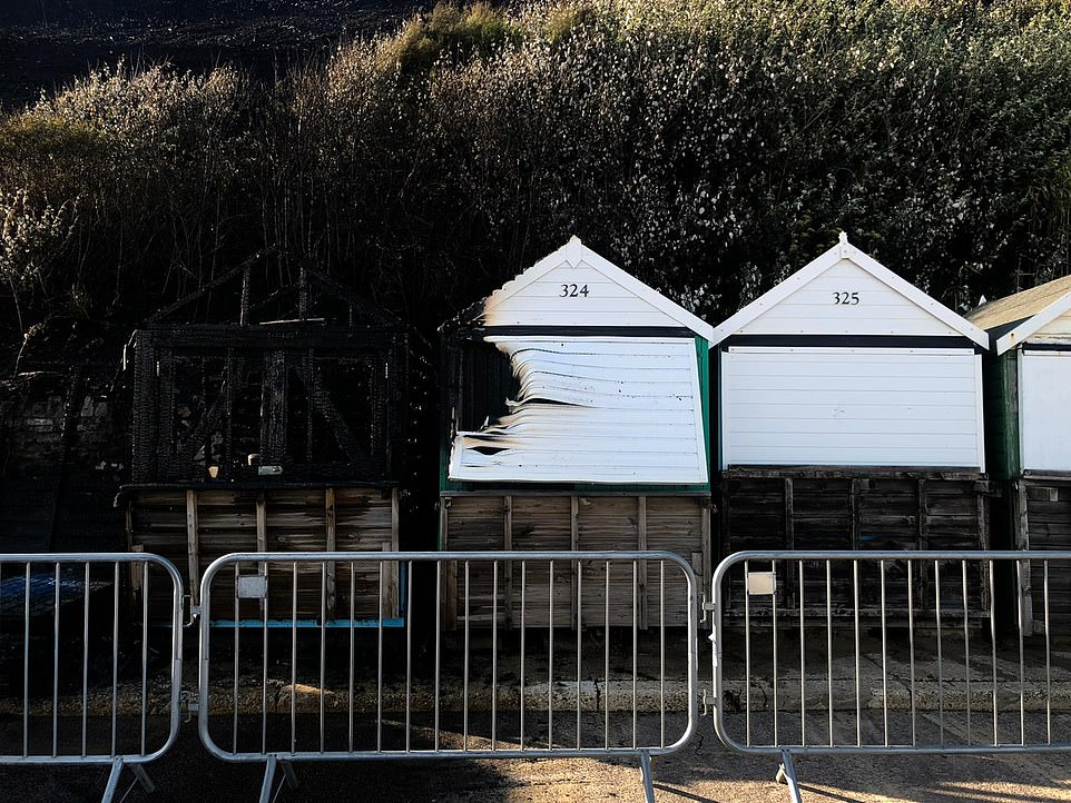 The remains of a neighbouring beach hut is seen to the right of where the burnt out hut formerly stood (on the far left), while another hut (centre) has had its left side severely damaged in the inferno