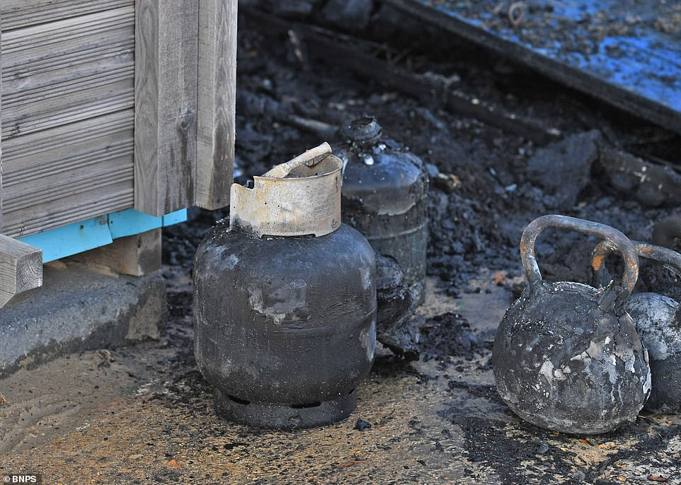 Burnt out gas canisters are seen in the aftermath among the charred remains of the timber-framed beach hut which caught fire