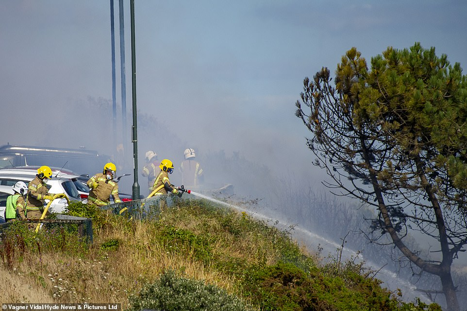 Firefighters tackle the blaze from the top of the cliff just yards away from the four-star Highcliff Marriott Hotel