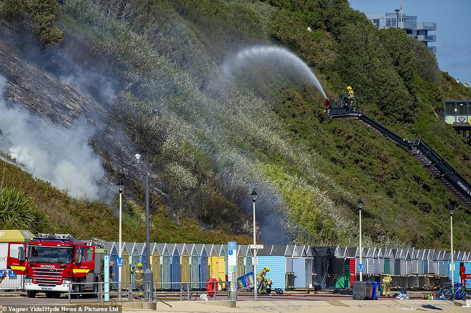 The scorched cliff-side being doused by a fireman inside a cherry picker yesterday afternoon - the burnt out huts can be seen on the promenade
