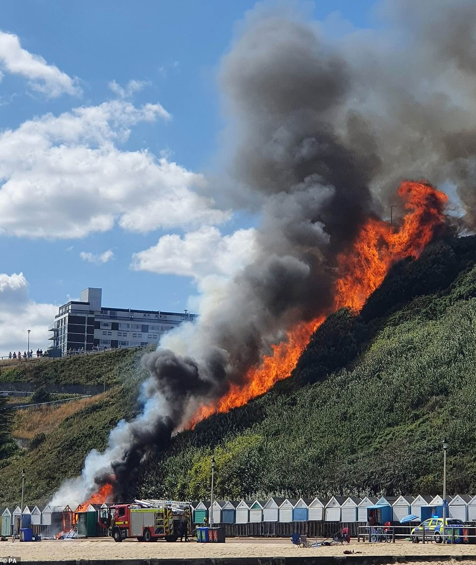Firefighters are battling a huge blaze on Bournemouth beach after three beach huts went up in flames