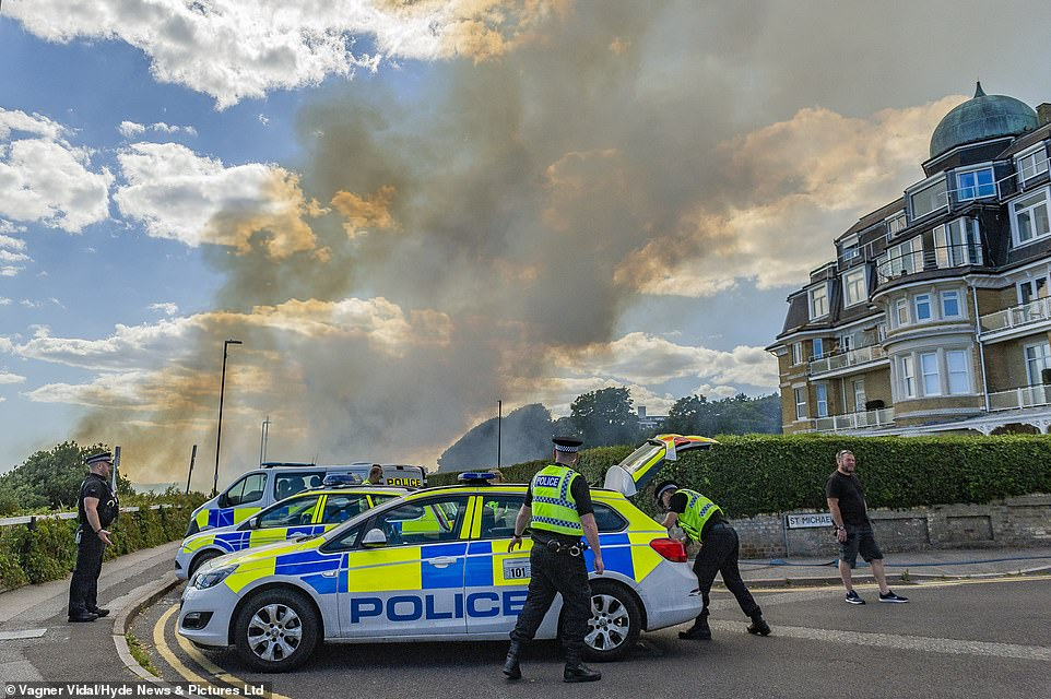 Police officers are photographed close to the carnage yesterday as the beach was evacuated