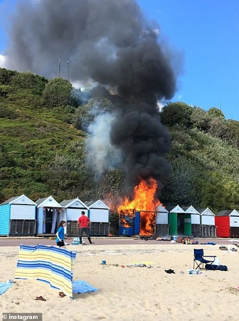 Dorset and Wiltshire Fire Brigade said: 'Dorset & Wiltshire Fire and Rescue Service is currently dealing with a fire on West Undercliff in Bournemouth, affecting three beach huts and approximately 100 sqm of heath on the cliff face'