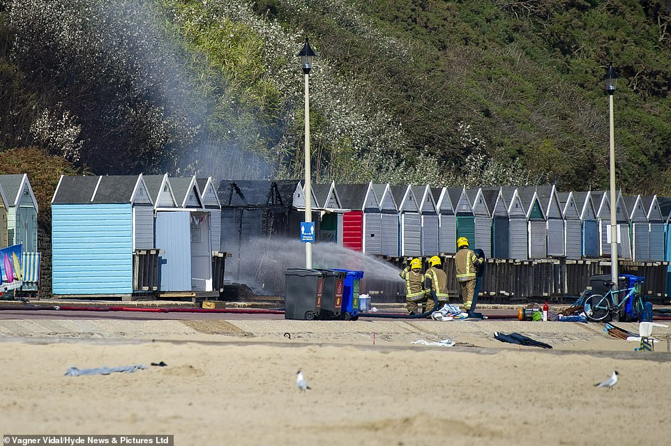 Firefighters spray the scorched huts with a hose after the beach was cleared of visitors