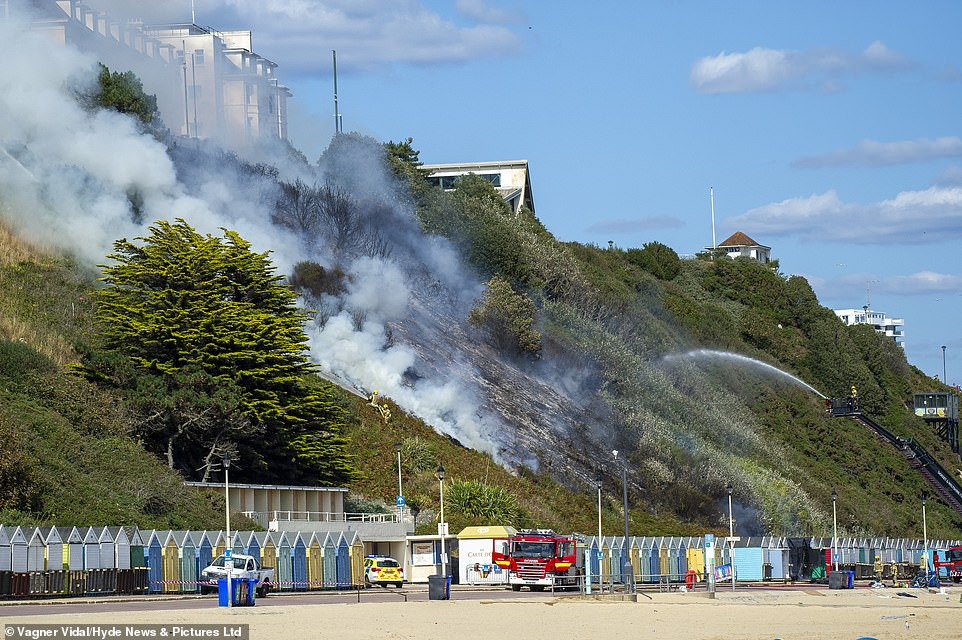 Firefighters douse the cliff face after bringing the worst of the fire under control yesterday afternoon