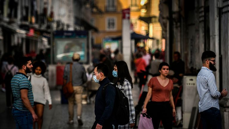 Some tourists wearing protective masks while walking around Lisbon, Portugal