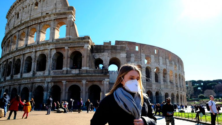 Tourist wearing a protective respiratory mask tours outside the Colosseo monument (Colisee, Coliseum) in downtown Rome on February 28, 2020 amid fear of Covid-19 epidemic. - Since February 23, more than 50,000 people have been confined to 10 towns in Lombardy and one in Veneto -- a drastic measure taken to halt the spread of the new coronavirus, which has infected some 400 people in Italy, mostly in the north. (Photo by Andreas SOLARO / AFP) (Photo by ANDREAS SOLARO/AFP via Getty Images)