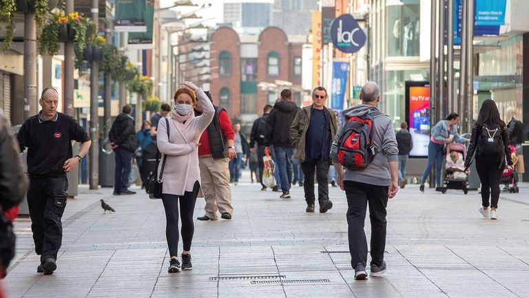 Some people wear face masks as they walk past shops in Dublin