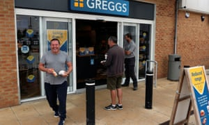 People are seen outside a Greggs store.