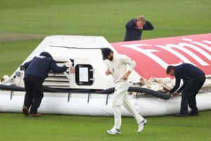 Woakes makes his way off whilst the ground staff put the covers on.
