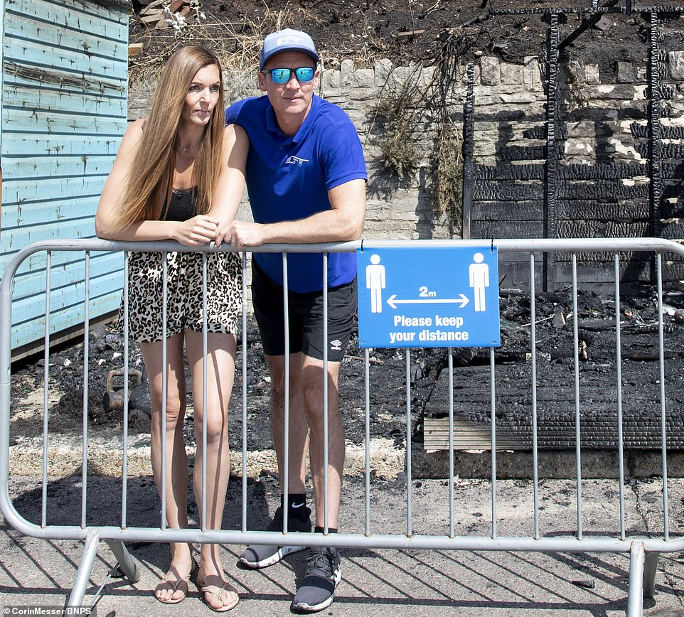 Fiona Tew (pictured with her husband Gavin in front of their burnt out hut today) was at the beach hut with her sister-in-law Lainey Norman, 39, and five children when her nephew rushed in saying he had been stung by a fish
