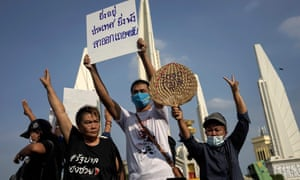 """Protesters hold a sign reading, """"The longer you stay, the more devastation to the country, please resign"""" as they take part in an anti-government demonstration in Bangkok on July 18, 2020."""