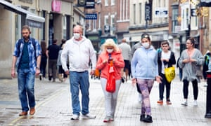A family in face masks walk along Coney Street, one of the main shopping streets in York, North Yorkshire.