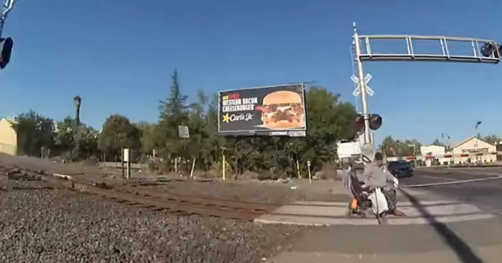 Video shows police officer pulling man in wheelchair off railroad tracks before oncoming train hits