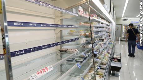 As evacuation advisers were issued due to Typhoon Heishen's policy, a man shopped near empty food shelves at a convenience store in Hitoyoshi, Kumamoto Prefecture, on September 6.