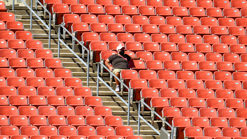 The man in the mask sits in a sea of empty chairs.