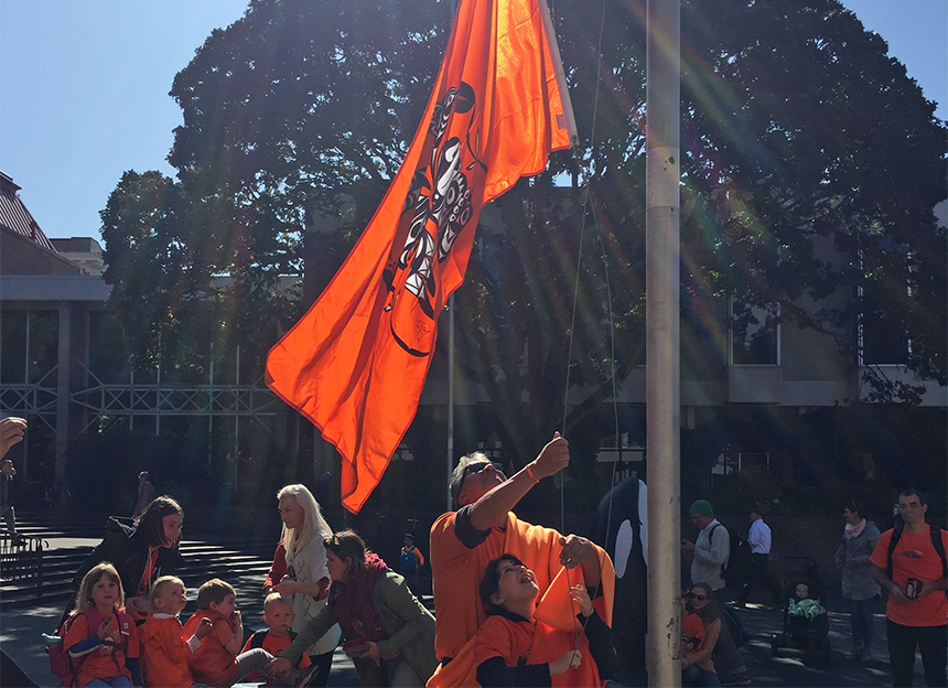 Hayley and her father successfully hoisted a huge orange flag on a flagpole.