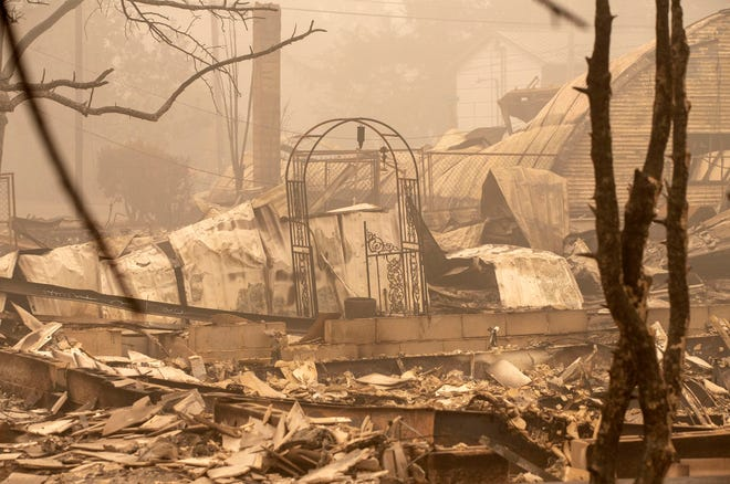 Remains of a house destroyed by a Beach Creek fire east of Salem, Oregon, are standing amidst smoke on September 13, 2020.