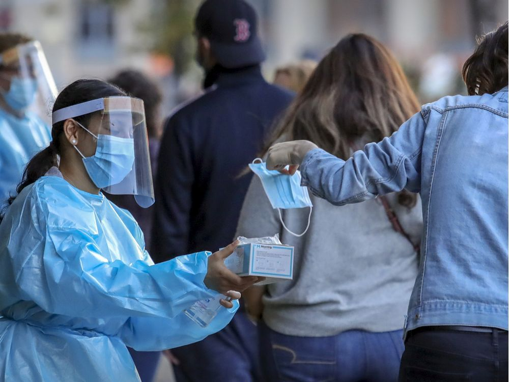 MONTREAL, QUE.: SEPTEMBER 24, 2020 -- Staff from Park Extension Covid-19 testing centre hands surgical mask to a woman waiting in line in Montreal Thursday September 24, 2020. (John Mahoney / MONTREAL GAZETTE) ORG XMIT: 65056 - 4406
