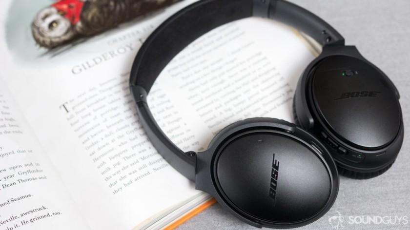 Bose Quiet Comfort II headphones are resting against the open notebook.