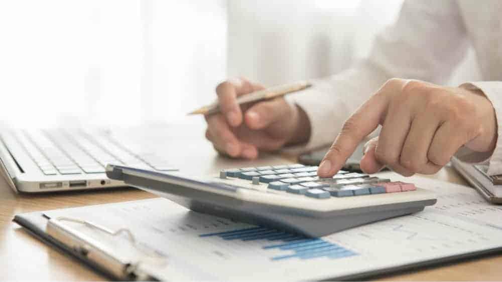 Businessman using calculator next to laptop