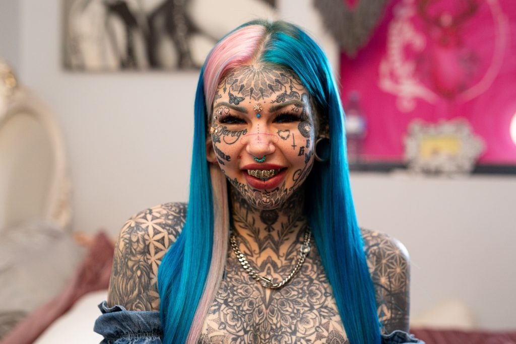 """BRISBANE, AUSTRALIA - MAY 28, 2020: AMBER LUKE, 25, from Brisbane, Australia has 600 tattoos covering her face and body. She first filmed with Truly last year, revealing her blue tattooed eyes which blinded her for three weeks. Since then, she has continued to add to her collection with stretched ear lobes, more tattoos, and plans to get a Brazilian Butt Lift. Her journey into body modification began when she was diagnosed with severe clinical depression at 16-years-old. She explained the reasons behind her extreme look to Truly: """"I know it sounds very materialistic that I want to change myself but imagine hating yourself so much that you couldn't even look in a mirror or step outside your house. It was just, it was a horrific way to live."""" Amber has now spent $50,000 on tattoos, and $70,000 overall on body modifications. She joked that the high cost makes her mum cry, but Amber doesn't """"plan on stopping anytime soon"""". Her next procedure will be a Brazilian Butt Lift, which she has gained 10 kilos for, as the fat will be injected into her butt. She said: """"A lot of people will give me scrutiny for this because, you know, 'Why not just go to the gym'?"""" Amber continued: """"I'm lazy, I'd rather pay the 15 grand."""" Now she feels much more content and has been with her partner Sam for six months. """"He is absolutely amazing,"""" she said. """"There's not anything that I do or say that scares him away."""" PHOTOGRAPH BY Joshua Maguire / Barcroft Studios / Future Publishing - NOTE: This Photo Can Only Be Used Within Context With The Information Provided In The Metadata (Photo credit should read Joshua Maguire/Barcroft Media via Getty Images)"""