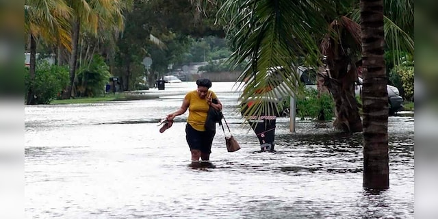 A woman walks through floodwaters on Monday, November 9, 2020, in the vicinity of Melrose Place in Fort Lauderdale, Fla.