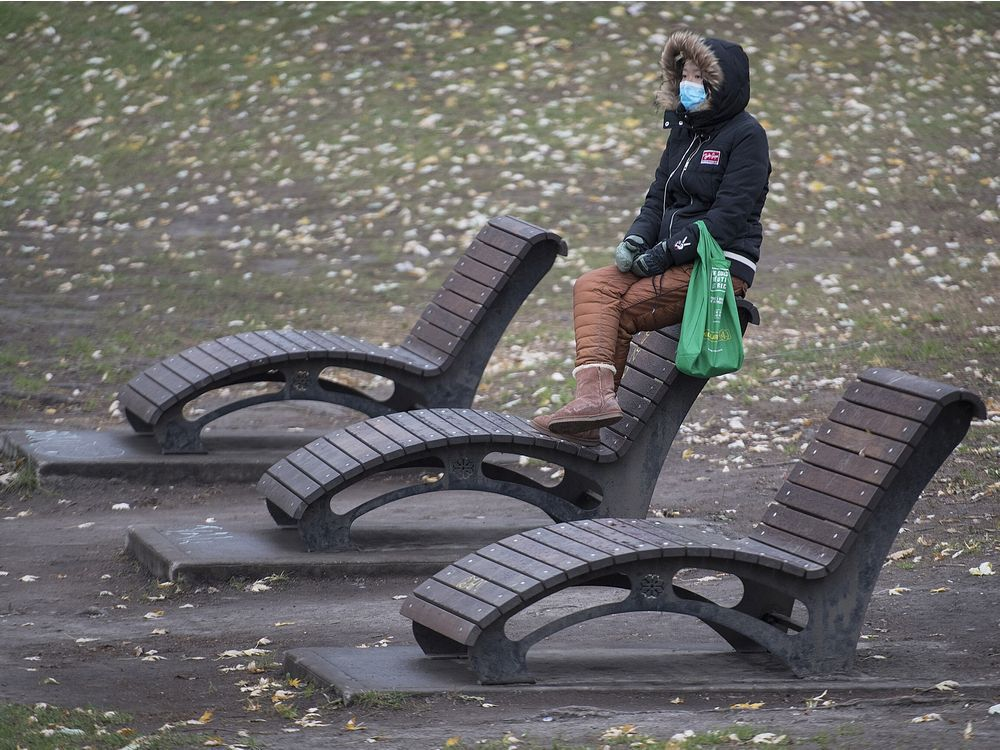 CP-Web. A woman wears a face mask as she sits in a park in Montreal, Sunday, November 15, 2020. THE CANADIAN PRESS/Graham Hughes ORG XMIT: GMH114