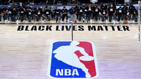 Members of the New Orleans Pelicans and Utah Jazz kneel before the Black Lives Matter logo on July 30, 2020 at the HP Field House in the ESPN Wide World of Sports Complex in Reunion, Florida.