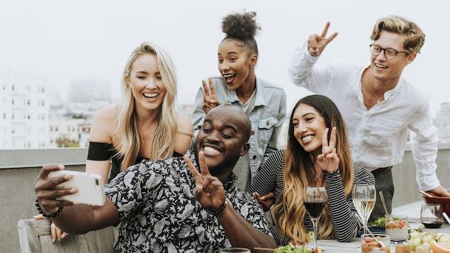 Cinq personnes posent pour un égoportrait de groupe à table.